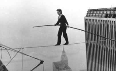 Walking the new product development tightrope between confidence and doubt.  Symbolized by a woman walking a tightrope across a big city skyscape.