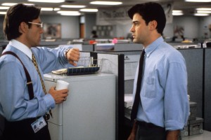 "Scene from the film ""Office Space"" -- two men talking, one manager and one employee, in a typical white collar work environment."
