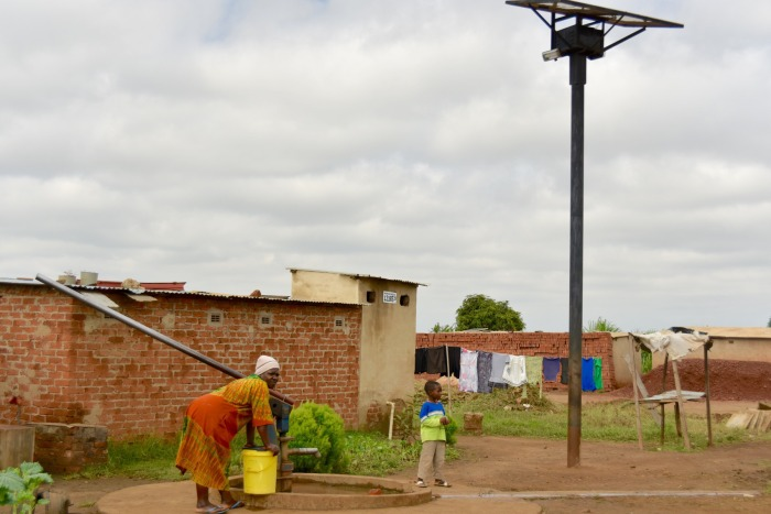 Several finished homes around a nearly complete streetlight installation that also illuminates a drinking-water well, enabling nighttime access to water.