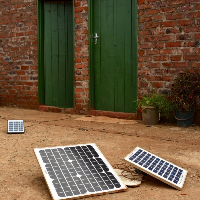 A trio of medium-sized solar panels strategically placed outside the doors of several homes sharing a courtyard.