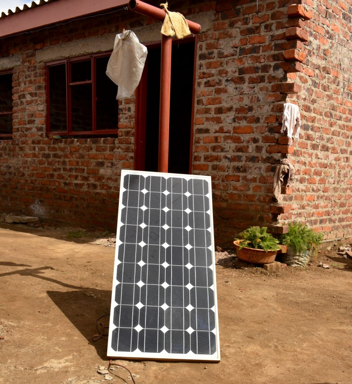 "A full-sized ""roof"" solar panel leaning up against a clothesline. Often roof-mounting panels is structurally challenging, so it is not uncommon to see these larger panels placed nearby on the ground."