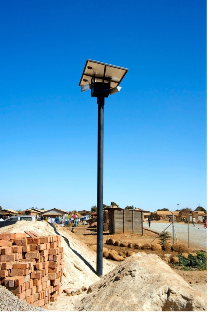 Solar-powered streetlights have been installed recently — here under construction — increasing public safety and providing light to the community.