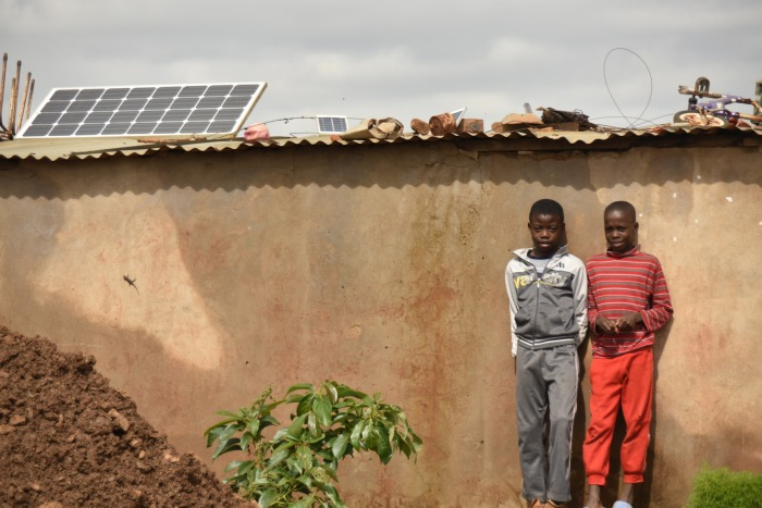 These two boys were hanging out when I walked by, and quickly chose a formal pose in front of their home, which has a large permanent solar panel mounted on the roof.