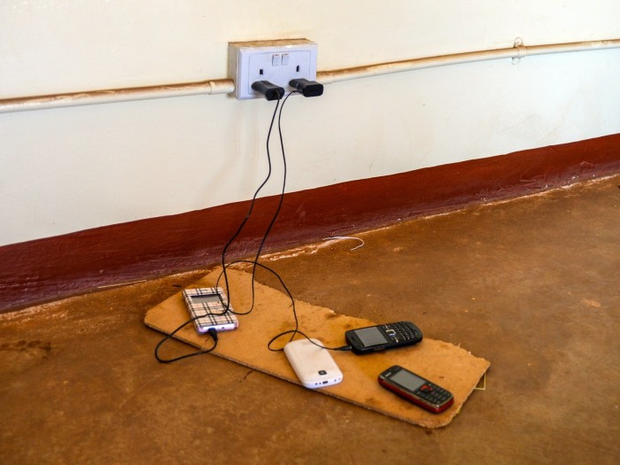 It is not uncommon to see one outlet shared by many members of a community. This outlet is in the community center, which is one of a small number of grid-connected structures. Note the variety of feature phones.